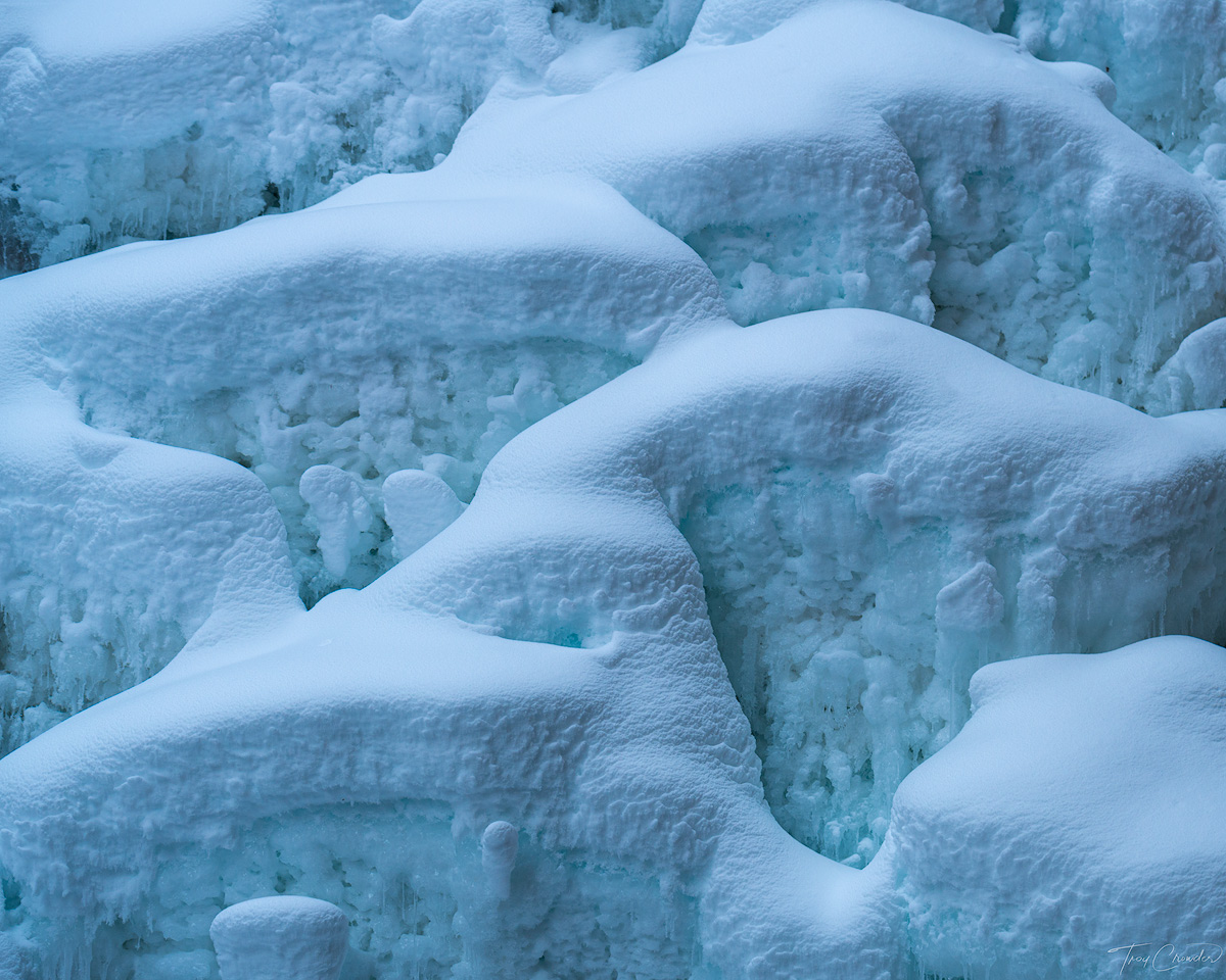 Repeating layers of snow pillows and ice in a frozen waterfall.
